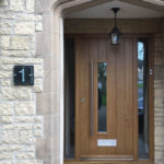 oak door and stone frontage featuring glass and slate house number handmade by Tim Carter